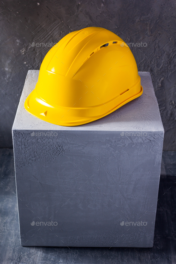 Helmet or hardhat on concrete cube or cement block background texture. Construction concept - Stock Photo - Images