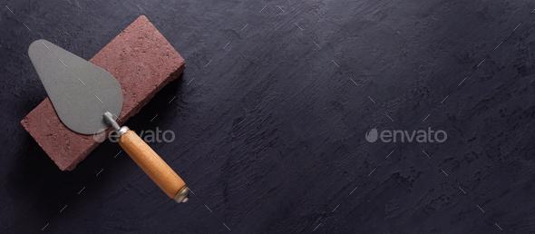 Construction trowel tool at brick at black background. Mason and bricks - Stock Photo - Images