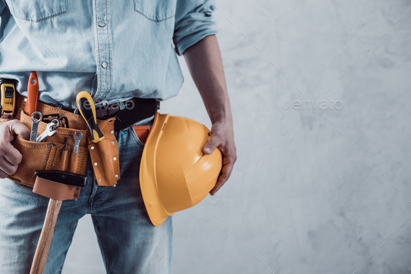 Worker man holding construction helmet tool near concrete or cement wall. Male hand and hard hat - Stock Photo - Images