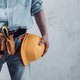 Worker man holding construction helmet tool near concrete or cement wall. Male hand and hard hat - PhotoDune Item for Sale