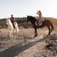Young couple riding horses doing excursion at countryside during sunset time - PhotoDune Item for Sale