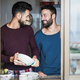 Gay male couple having tender moment while washing dishes inside home kitchen - PhotoDune Item for Sale