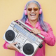 Happy senior woman listening music while holding boombox vintage stereo - Focus on face - PhotoDune Item for Sale