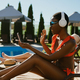 Woman in headphones listening to music on sun bed - PhotoDune Item for Sale