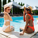Girlfriends sitting at the edge of pool, back view - PhotoDune Item for Sale