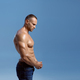 Male athlete shows his biceps in studio, side view - PhotoDune Item for Sale