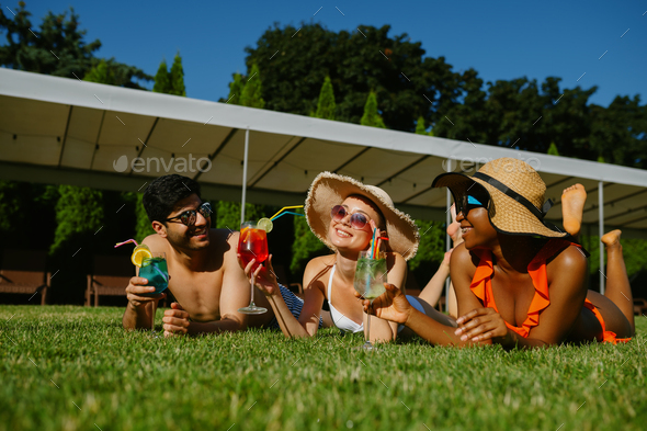 Cheerful friends rest on the grass near the pool - Stock Photo - Images