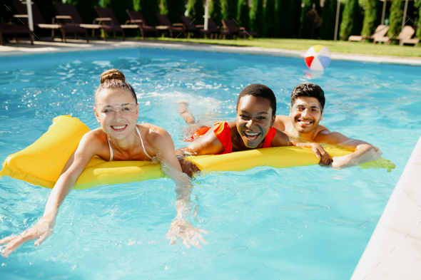 Smiling friends swim on a mattress in the pool - Stock Photo - Images