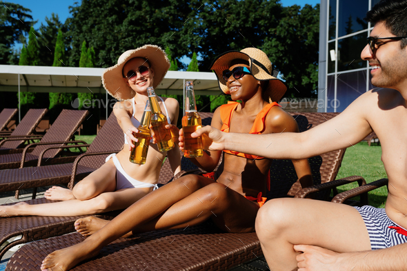 Friends clink bottles with beer near the pool - Stock Photo - Images