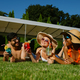 Cheerful friends rest on the grass near the pool - PhotoDune Item for Sale