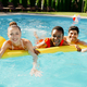 Smiling friends swim on a mattress in the pool - PhotoDune Item for Sale