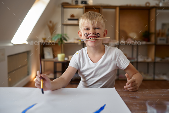 Little boy drawing with gouache on his face - Stock Photo - Images
