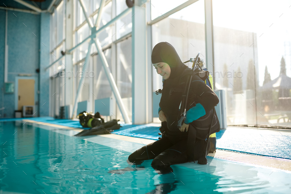 Male diver in scuba suit sitting at the poolside - Stock Photo - Images