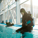 Male diver in scuba suit sitting at the poolside - PhotoDune Item for Sale