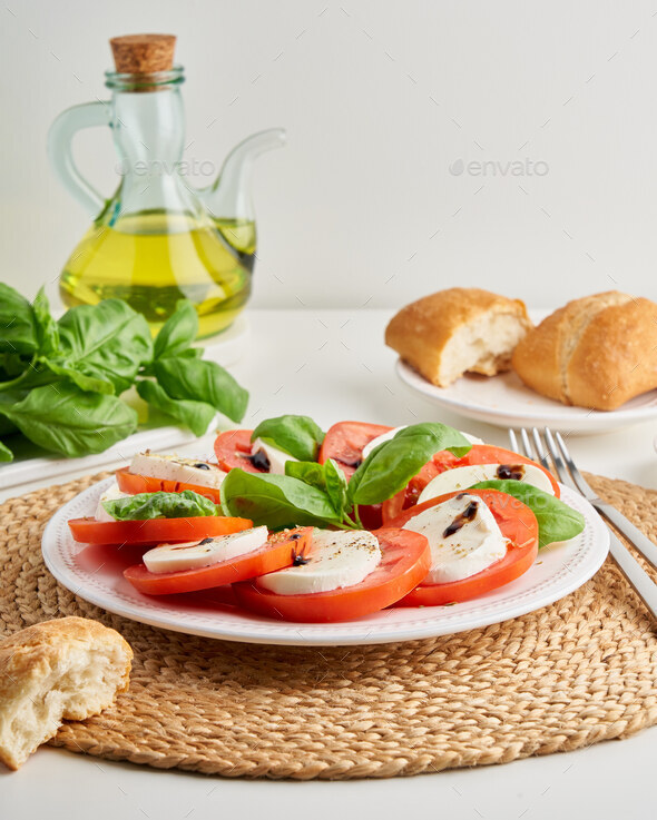 Italian caprese salad with sliced tomatoes and mozzarella. Mediterranean cuisine. Delicious meal - Stock Photo - Images