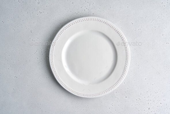 Empty white ceramic plate on light background. Copy space, top view, horizontal, closeup - Stock Photo - Images