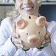 Hands of happy woman showing piggy bank to save money. Concept of saving money - PhotoDune Item for Sale