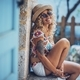 Portrait of beautiful smiling hipster young woman in sunglasses and straw hat sitting outdoors - PhotoDune Item for Sale