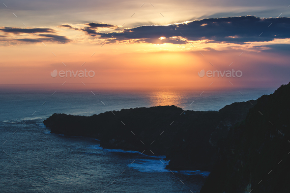 Sunset cloudy sky over the ocean and cliff, Bali - Stock Photo - Images
