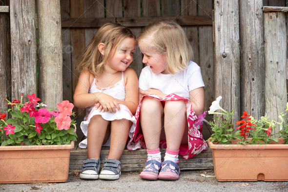 Two Young Girls Playing in Wooden House - Stock Photo - Images