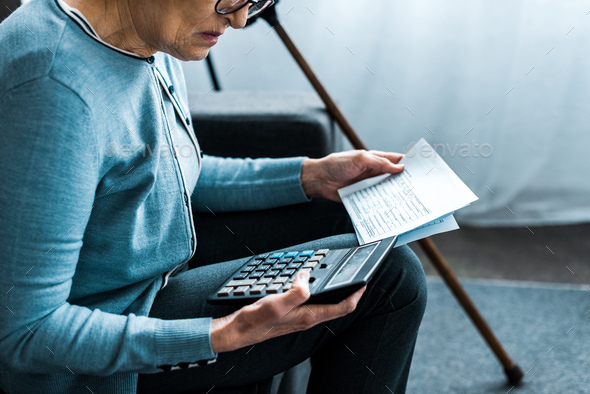 cropped view of senior woman sitting on couch with calculator and counting bills at home - Stock Photo - Images