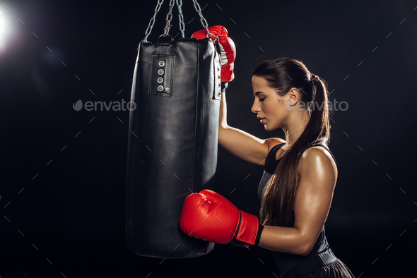 Side view of female boxer in red boxing gloves training with punching bag - Stock Photo - Images