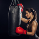 Side view of female boxer in red boxing gloves training with punching bag - PhotoDune Item for Sale