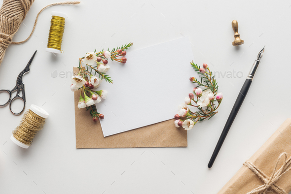 top view of empty blank with brown envelope, ink pen, flowers, scissors, stamp, spools of thread and - Stock Photo - Images