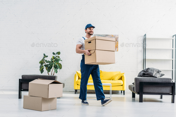 mover in uniform carrying cardboard boxes in modern apartment - Stock Photo - Images