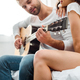 selective focus of man playing acoustic guitar near woman - PhotoDune Item for Sale