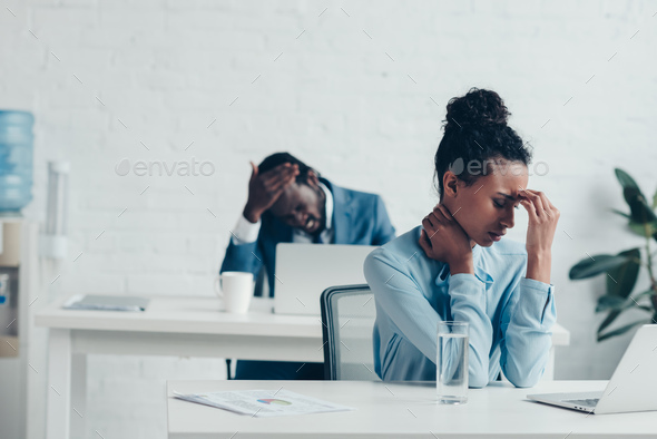 african american managers sitting at workplaces and suffering from headaches - Stock Photo - Images