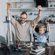 happy father and son with raised hands looking at rocket model at home - PhotoDune Item for Sale