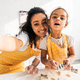 camera point of view of smiling african american mother and daughter in aprons preparing cookies in - PhotoDune Item for Sale
