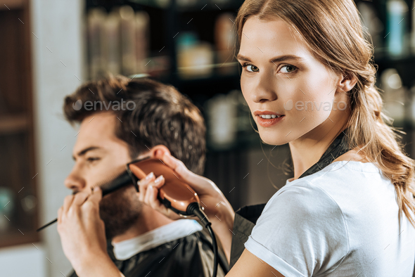 attractive hairstylist looking at camera while trimming hair to male client in beauty salon - Stock Photo - Images