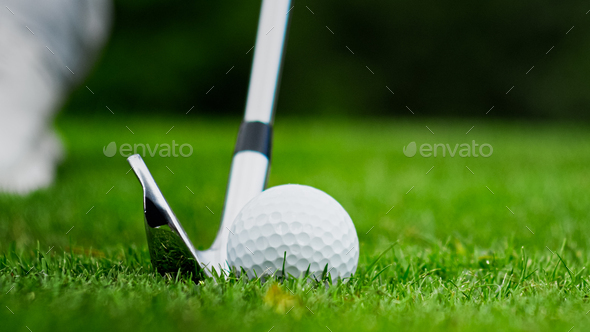 Golf club kicking the ball on green grass - Stock Photo - Images