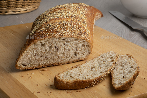 Traditional sourdough bread in a special shape with seeds on a cutting board - Stock Photo - Images