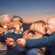 Happy senior friends celebrating with sparklers outdoor - PhotoDune Item for Sale