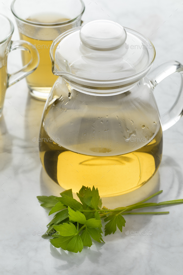 Glass teapot with lovage tea and a fresh twig of lovage - Stock Photo - Images