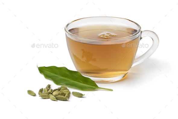 Glass cup with Cardamom tea and a heap of cardamom seeds in front on white background - Stock Photo - Images