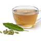 Glass cup with Cardamom tea and a heap of cardamom seeds in front on white background - PhotoDune Item for Sale