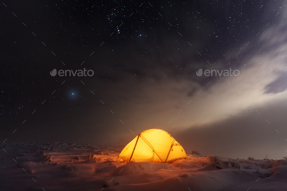Yellow tent lighted from the inside against the backdrop of glowing city lights - Stock Photo - Images