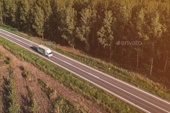Aerial view of lorry truck on the road through green forest landscape in summer afternoon, drone pov - Stock Photo - Images