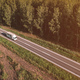 Aerial view of lorry truck on the road through green forest landscape in summer afternoon, drone pov - PhotoDune Item for Sale