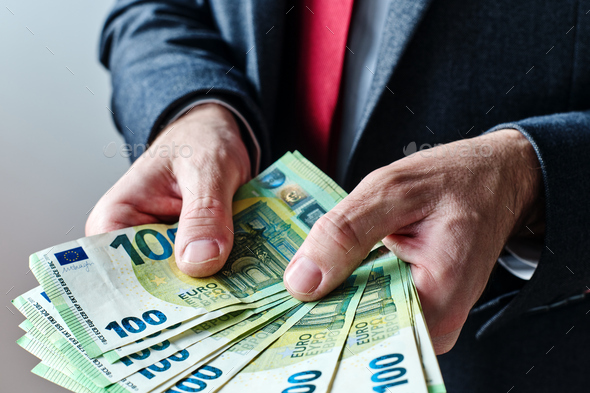 Businessman offering payment in new hundred euro banknotes - Stock Photo - Images