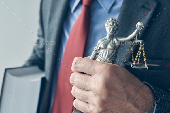 Attorney holding law book and statue of Lady Justice - Stock Photo - Images