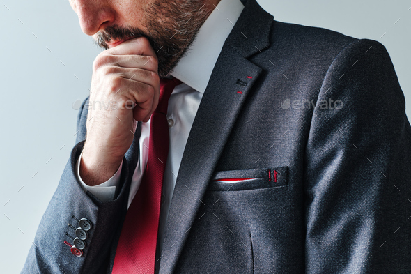 Serious pensive businessman contemplating with hand on chin - Stock Photo - Images