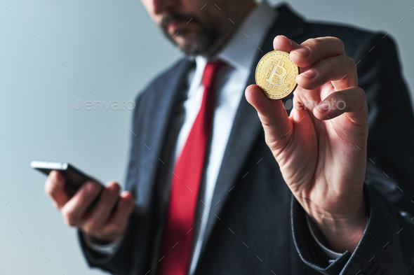 Businessman using mobile smart phone app for Bitcoin mining - Stock Photo - Images