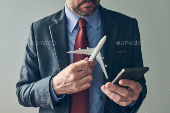 Businessman booking airplane flight ticket online using mobile phone application - Stock Photo - Images