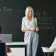 Smiling young teacher having mathematics lesson standing at chalkboard. - PhotoDune Item for Sale