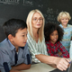 Happy teacher with diverse schoolkids having maths lesson sitting at desk. - PhotoDune Item for Sale